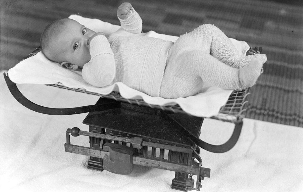 Baby wordt gewogen op ene babyweegschaal bij het consultatiebureau