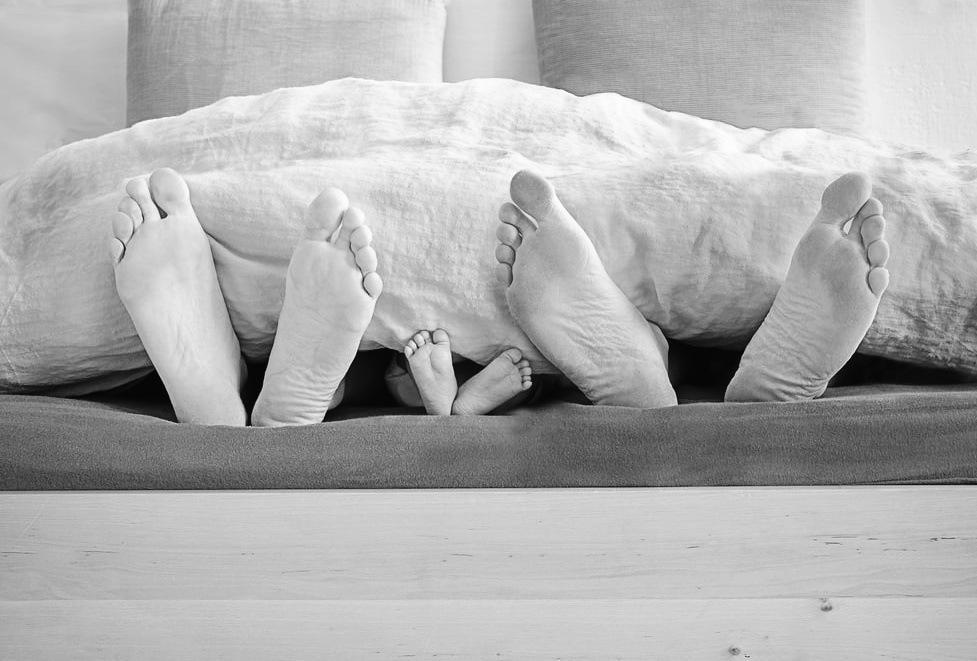Babyvoeten op bed tussen papa en mama